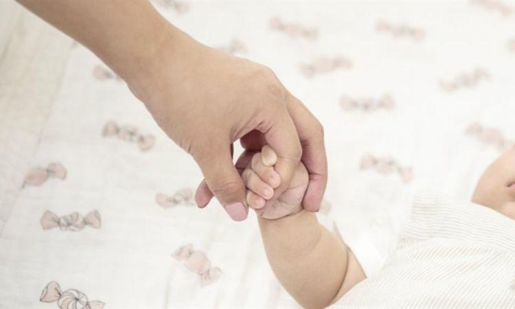 Recién nacido sostiene la mano de su madre
