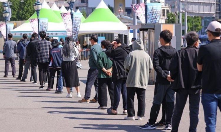 Personas haciendo cola para tomarse la prueba de COVID-19 en Seúl